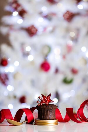 Chocolate Muffin, decorated with red star, golden spoon and defocused Christmas lights background. Christmas dessert concept