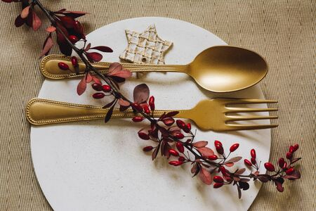 Holiday Gold place setting, white plate of concrete, with fork and golden spoon. Christmas or tanksgiving  dinner. From above