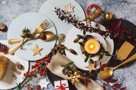 Holiday table setting, funny Christmas table with ornaments and natural berries, on blue table