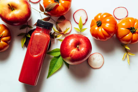Red smoothie drink in bottle near ripe apples tomatoes and beets. Detox diet for healthy body and mind. health food concept.somoothie red, botle, furits beets, from above