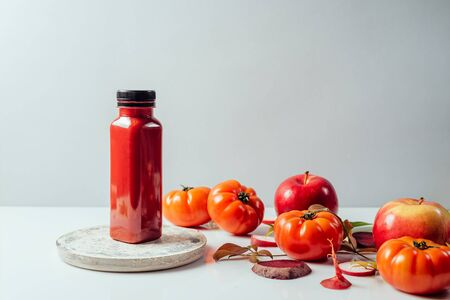 Red smoothie drink in bottle near ripe apples tomatoes and beets. Detox diet for healthy body and mind. health food concept. Front view on grey background