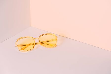 Modern yellow sunglasses in front of the corner of the wall background with copy space. Product photograph of minimalist concept with room for text, front view Stock Photo