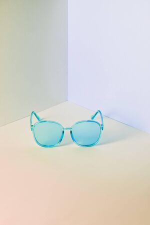 Modern blue sunglasses in front of the corner of the pastel wall background with copy space. Product photograph of minimalist concept with room for text, front view Stock Photo