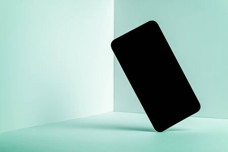 Minimalist modern smartphone mockup for presentation, in perspective front of the corner angle of the wall, with overlapping shadows on green background. application display, information or graphics