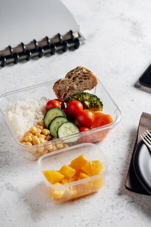 Healthy food in lunch box, on working table with the tablet. Basmati rice with chickpeas, broccoli, tomato and carrot, bread and fruit for dessert. eating at workplace. Homemade food concept in the office or study place