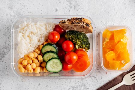 Healthy food in lunch box, on working table. Basmati rice with chickpeas, broccoli, tomato and carrot, bread and fruit for dessert. eating at workplace. Homemade food concept in the office or study place