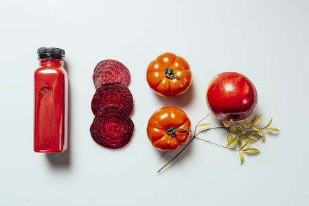Red smoothie drink in bottle near ripe apples tomatoes and beets. Detox diet for healthy body and mind. health food concept. On light background