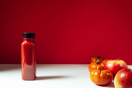 Red smoothie drink in bottle near ripe apples and tomatoes  Detox diet for healthy body and mind. health food concept. Front view