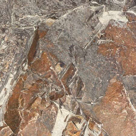 Coarse and brute natural granite stone texture with cracks. Gray and light brown tones.