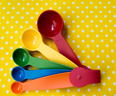 spoon yellow: colorful measuring spoon on yellow background Stock Photo