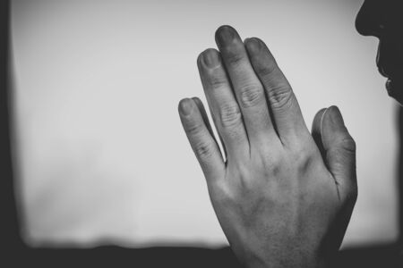 A woman is praying by her hands and white - black background. Praying hands. Zdjęcie Seryjne