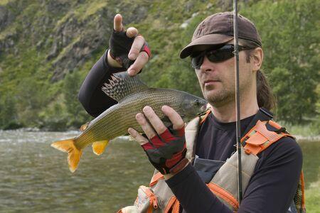 grayling: Pescador que sostiene un gran t�malo