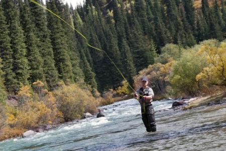 釣り: フライフィッシングの釣り人は水に立っている間鋳造
