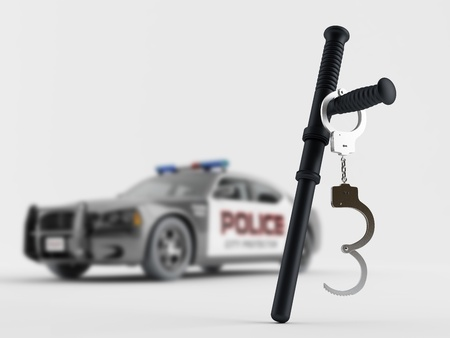 Baton and handcuffs on the background of a police car