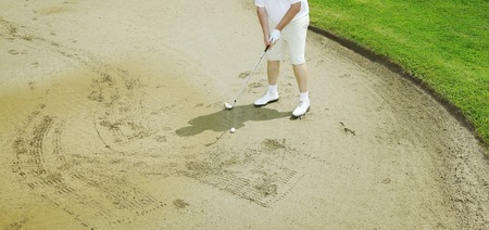 golfing: Picture of a man golfing in the sand. Stock Photo