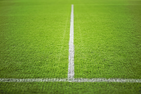 Football green field with white stripes.