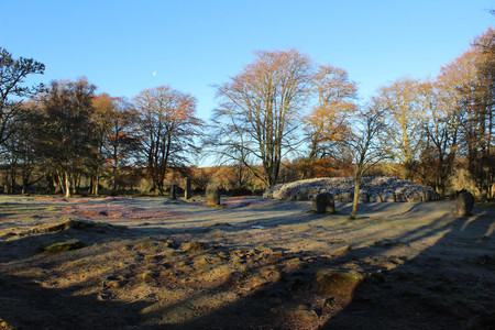 Moody sunset view of Clava Cairns in the Scottish Highlands during late fall or early winter with bare trees and colored leaves on the ground.