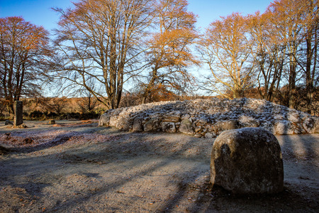 Close-up view of Clava Cairn near Inverness Scotland on a winters morning with frost and sunlight beaming thrown the trees creating shadows.