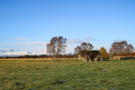 Landscape of Culloden Moor and Leanach House on an autumn or early winters day with snow capped mountains in the distance. Stock Photo