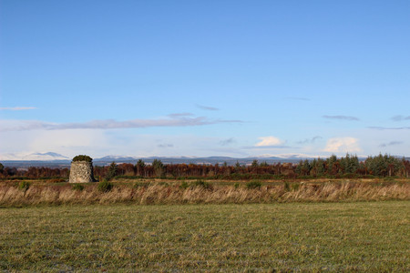 View of Culloden Moor, memorial Cairn or grave for the clans and snow capped mountains in the background in an autumn or early winters day. Stock Photo