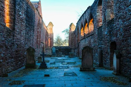 Interior of Beauly Priory Ruins with autumn leaves and the glow of sunset beaming through the window holes. Stock Photo