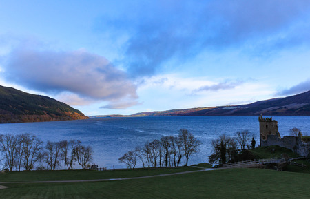 Panoramic view of Loch Ness and Urquhart Castle ruins during sunset in the autumn.