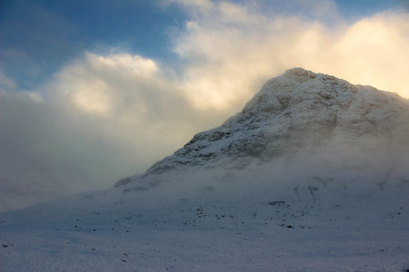 Magnificent view of snowy Glen Etive in Scotland back lit by the sun with clouds and mist surrounding it.