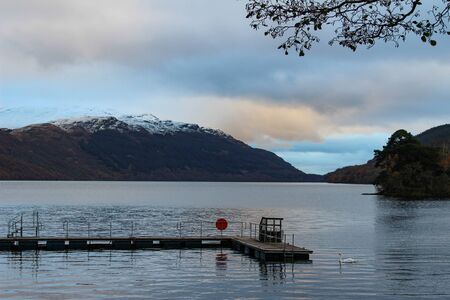 Beautiful view of Loch Lomond and snow capped mountains with a swan and boating dock during sunset in early winter.