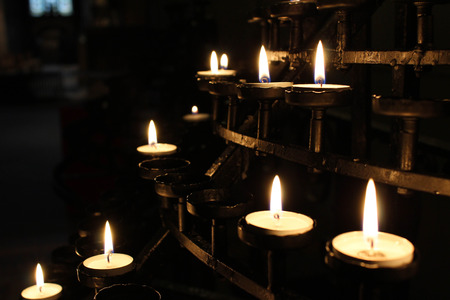 Beautiful votive prayer candles lit in a brass sconce holder in a church. Stock Photo