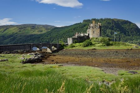Eilean Donna Castle seen with a rare low tide with foot bridge and Scottish Flag flying.