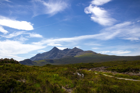 Centered peaks and hiking trail visible in a magnificent landscape of the Cuillin Mountains and Tir Nan Iolaire or Land of Eagles on the Isle of Skye in Scotland.