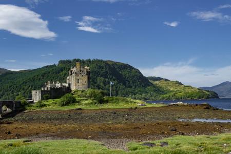 Castillo de Eilean Donan durante la marea baja en el verano con un cielo despejado, montañas y Loch mirando a través.