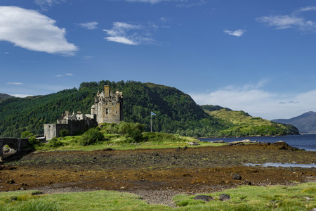 Eilean Donan Castle during low tide in the summer with a clear sky, mountains, and Loch peeking through.
