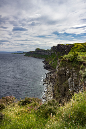 Gorgeous Vertical view of the sea-cliffs of the Trotternish Peninsula across from Kilt Rock on the Isle of Skye in Scotland. Stock Photo