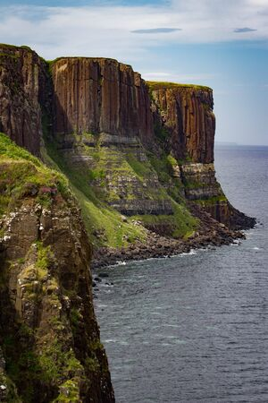 Gorgeous vibrant vertical view of Kilt Rock on the Trotternish peninsula of the Isle of Skye in Scotland.