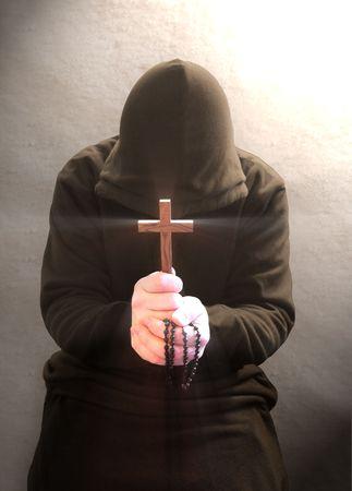 monasteri: Un monaco pregando con crocefisso e un rosario in mano.