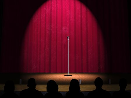 A microphone on a stage with a spotlight on it and an audience in the foreground.