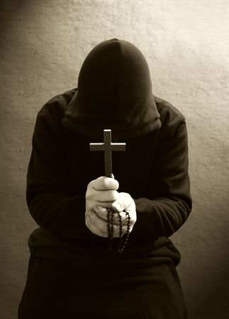 A monk praying with a rosary and crucifix in his hand. photo