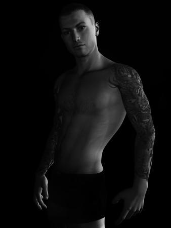 slip homme: Un beau jeune homme avec des tatouages sur les bras.