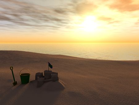 bucket and spade: A bucket, spade and sand castle on a beach at sunset. Stock Photo