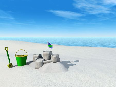A bucket, spade and sand castle on a beach by the sea on a sunny summer day.