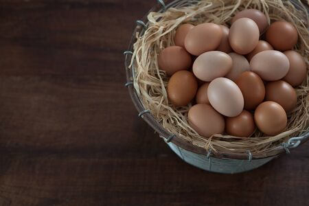 Fresh farm chicken eggs in metal wire basket on wooden table Stock Photo