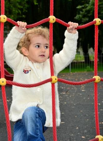 climbing frame: Giovane arrampicata bambino su un telaio rete di arrampicata Archivio Fotografico
