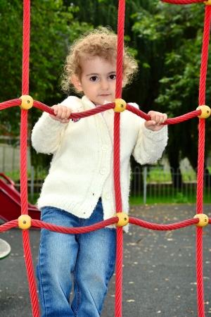 climbing frame: Giovane bambino che si arrampica su un telaio di rete di arrampicata