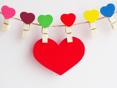Closeup hanging big red heart made from paper on white paper background with colorful clips and negative space for text, Valentine's Day concept, love and romance concept Foto de archivo
