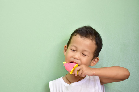 Cute little Asian boy in white t-shirt enjoys eating homemade ice pop on a light vintage green background Stock Photo