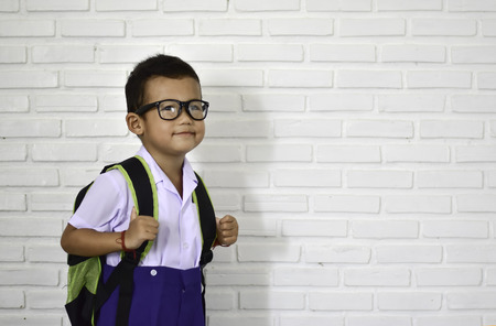 Back to school, little Asian kindergarten boy in school uniform wearing glasses carrying a bag and a notebook ready to go to school, first day to school with copy space for text 스톡 콘텐츠