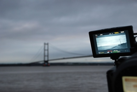 yorkshire and humber: Humber Bridge being filmed from the river bank at dusk on a professional video camera