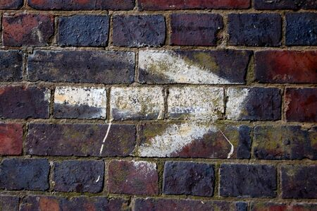 defaced: White arrow pointing right, painted on a brick wall