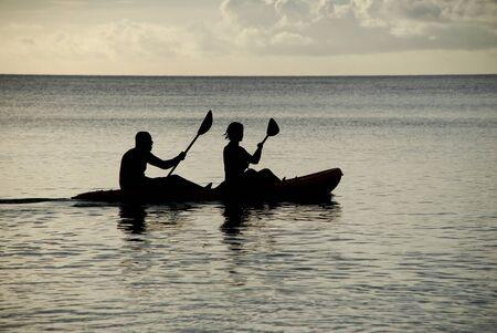 ocean kayak: Hombre y mujer siluetas en el mar en un kayak